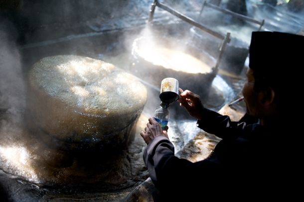 A man tests the latest batch of sugar cane, being boiled into a sugary froth East Java Indonesia
